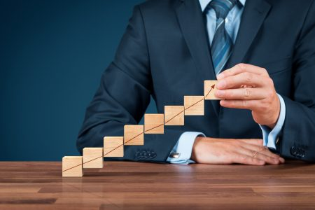 Businessman with wooden cubes with increasing graph