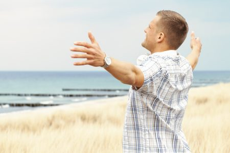 Man at the seaside spreads his arms