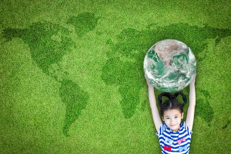 Sustainable world environment and CSR with people campaign concept with girl kid raising earth on green lawn: Element of the image furnished by NASA