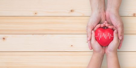Hands of a child and a grown-up holding a red heart with a white pulse sign