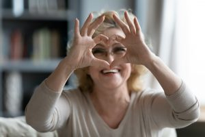 Elderly woman sitting on couch showing heart symbol with fingers